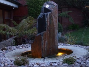 Monolith stone waterfeature at night